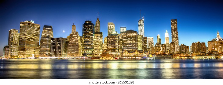 New York City. Magnificent Manhattan downtown skyline at dusk with skyscrapers illuminated over East River panorama.