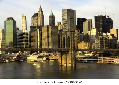 New York City Manhattan with Brooklyn Bridge and skyscrapers over Hudson River in the morning.