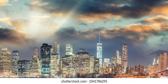 New York City Manhattan downtown skyline at dusk with skyscrapers illuminated over river panorama.