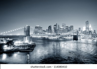 New York City Manhattan downtown skyline aerial view black and white at dusk with skyscrapers lit over East River with reflections.