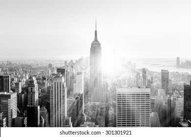 New York City. Manhattan downtown skyline with illuminated Empire State Building and skyscrapers at sunset. Vertical composition. Sunbeams and lens flare. Black and white image.