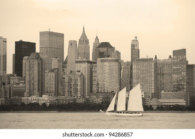 New York City Manhattan downtown skyline with boat at sunset over Hudson River panorama black and white