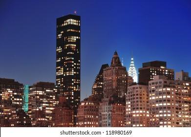 New York City Manhattan midtown skyline at night over East River.