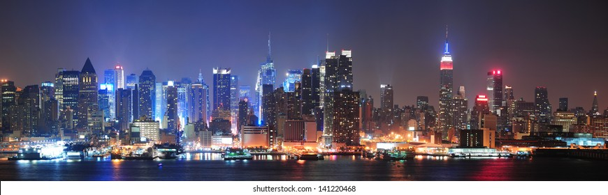 New York City Manhattan midtown skyline at night with skyscrapers lit over Hudson River with reflections.