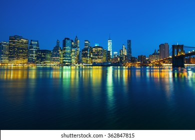 New York City Manhattan midtown at dusk with skyscrapers illuminated over east river