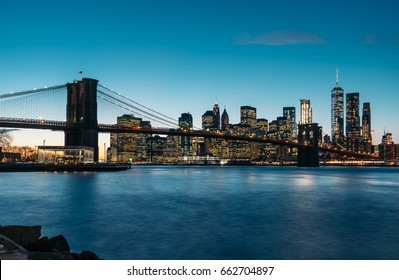 New York City Manhattan midtown at sunset with Brooklyn Bridge.