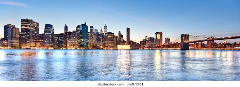 New York City Manhattan skyline panorama and cityscape at twilight with Brooklyn Bridge