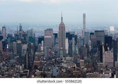 New york city and manhattan skyline at dusk with cloudy sky and lights. Photographed from the Freedom Tower facing North