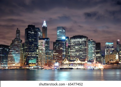 New York City Manhattan skyline panorama view at night with office building skyscrapers illuminated over Hudson River