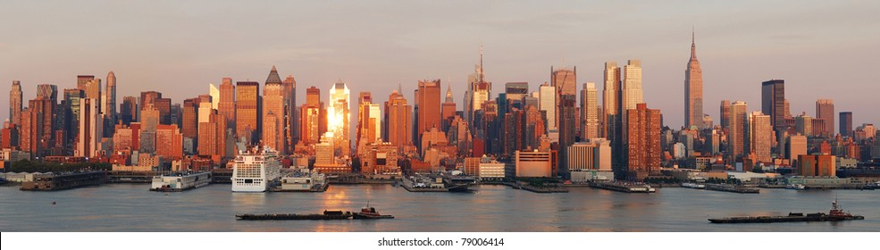 New York City Manhattan skyline panorama at sunset with empire state building and skyscrapers with reflection over Hudson river.
