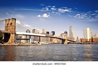 New York City Manhattan skyline with Brooklyn Bridge and skyscrapers over Hudson River in the morning after sunrise.