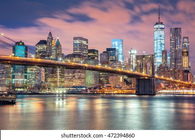 New York City - Manhattan with skyscrapers  and famous Brooklyn Bridge, great illumination and moody clouds