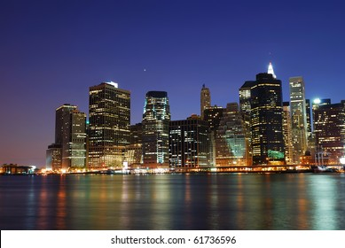 New York City Manhattan urban skyline over Hudson River with office skyscrapers building in at dusk illuminated with lights at night