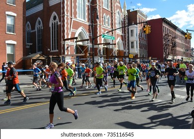 New York City Marathon on Manhattan Avenue at Milton Street in Greenpoint, Brooklyn with the Church of Saint Anthony in the Background - November 6, 2016.