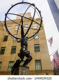 NEW YORK CITY - MARCH 25, 2021: Atlas statue by Lee Lawrie with face mask in front of Rockefeller Center in midtown Manhattan during Coronavirus pandemic in New York