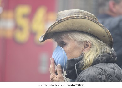 NEW YORK CITY - MARCH 26 2015: an explosion & fire thought to caused by a natural gas leak destroyed three brownstones on 7th St leaving 14 people injured & two missing. Resident with mask