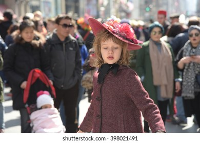 NEW YORK CITY - MARCH 27 2016; Easter Sunday was marked by the annual Bonnet Parade, filling 5th Avenue with hundreds of colorful hats & costumes. Dancing girl in flowered hat