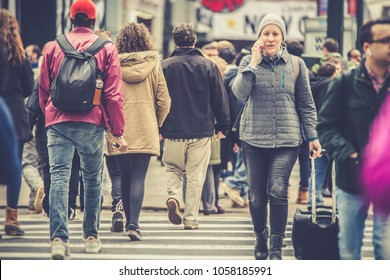 NEW YORK CITY - MARCH 29, 2018:  Busy New York City street scene of diversity of pedestrian people crossing the street in Midtown Manhattan on 34th Street Herald Square.