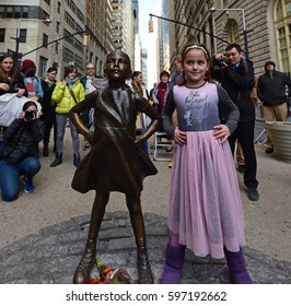 """NEW YORK CITY - MARCH 9 2017: A bronze statue entitled """"Fearless Girl"""" by sculptor Kristen Visbal was officially unveiled in Lower Manhattan, opposite the Wall Street Bull."""