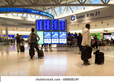 NEW YORK CITY - MAY 17, 2017:  View of the JetBlue Terminal 4 at John F. Kennedy International Airport aka JFK with travelers and arrival departure board.