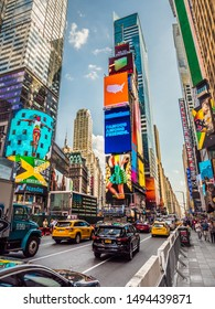 New York City, New York - May 19th, 2017: Traffic makes its way through the bustling busy streets in the center of Times Square as people pass by on the sidewalk protected by concrete barricades.