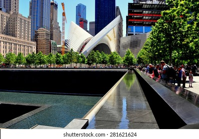 New York City - May 23, 2015:  9/11 Memorial north tower footprint with cascading waterfalls and the rising Santiago Calatrava PATH Transportation Center with its distinctive soaring white wings  *