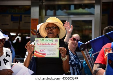 NEW YORK CITY - MAY 28 2016: Coney Island's landmark establishment Nathan's Famous celebrated its centennial anniversary with 5 cent hot dogs. Woman displays anniversary certificate