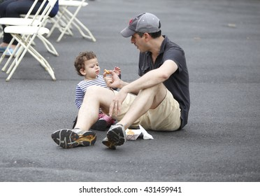 NEW YORK CITY - MAY 30 2016: Green-Wood Cemetery staged it's 28th annual Memorial Day concert by the Symphonic Orchestra at 3rd Street. Father gives little boy wiener