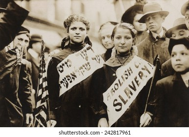 New York City May Day celebration of the international labor day. Two girls in the parade combined carrying an American flag, the slogan ABOLISH CHILD SLAVERY!! In English and Yiddish. 1909.