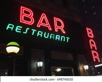 New York City Nighttime NX Establishing Shot CV of Bar Pub. Night exterior photograph of vintage neon sign. New York people go out at night to have fun, drink alcohol, go out on date, get together