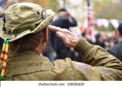 NEW YORK CITY - NOVEMBER 11 2015: New York City's Veterans Day parade was led by the US navy as this year's featured service. Veteran in cammo fatigues salutes during rendition of Star Spangled Banner
