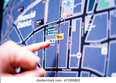 NEW YORK CITY, NY -18 april 2017: The tourist looks at the map of New York and shows by the finger where he is now. New York has an extensive system of metro lines and bus services.