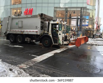 New York City, NY - January 26, 2016: New York City sanitation truck with a snow plow completes snow removal cleanup after Blizzard Jonas drops over two feet of snow in the tri-state area.