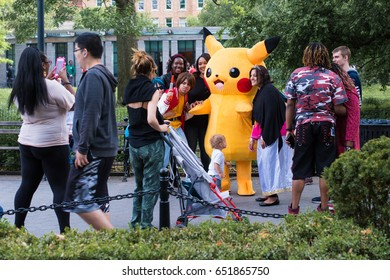 New York City, NY, May 27, 2017: Pikachu shows up in Washington Square Park, and fans run over to hug him and take photos.