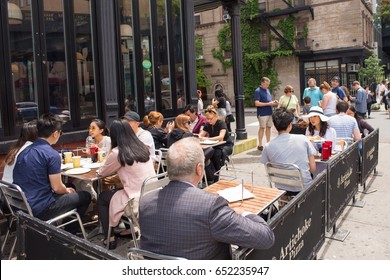 New York City, NY, May  28, 2017: People enjoying lunch on the patio of a restaurant in the Chelsea neighborhood. In 2017, more than thirty eight thousand people lived in Chelsea.