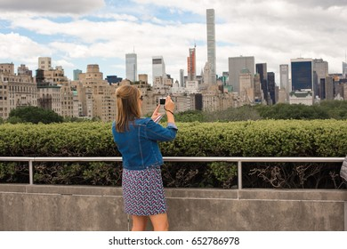 New York City, NY, May 27th, 2017: Beautiful woman stops to take a photo of the stunning New York City skyline visible from the roof of the Metropolitan Museum of Art, a famous landmark in New York.