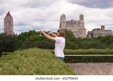 New York City, NY, May 27th, 2017: Attractive tourist takes a photo of his wine glass in front of the stunning NYC skyline, on the roof of the Metropolitan Museum of Art, a popular tourist destination