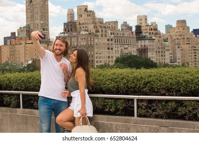 New York City, NY, May 27th, 2017: Beautiful couple poses for a photo on the roof deck of the Metropolitan Museum of Art. The Met attracts tourists and locals alike, offering stunning city views.