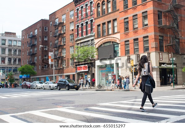 New York City, NY, May  28, 2017: A stylish woman crosses the street in the fashionable Chelsea neighborhood in Manhattan. She wears stylish fitness clothes with a cutout top.