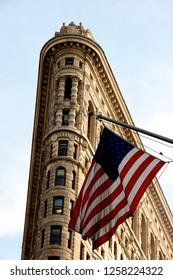 NEW YORK CITY, NY - SEPTEMBER 9, 2012: 22 story Flatiron apartment building on a triangular block of land on 5th Avenue, Manhattan, NY with the flag of the United States of America (USA)
