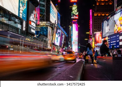 New York City, NY, United States - June 2, 2019: Night time shot of cars and pedestrians passing through Times Square in Manhattan.