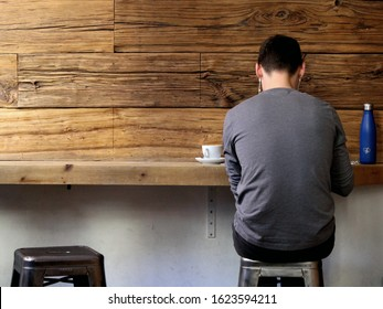 New York City, NY / United States of America - January 6 2020: a young man sits alone at the bar table of a cafe on a chair with an empty one nearby, with a white cup of coffee, facing a wooden wall.