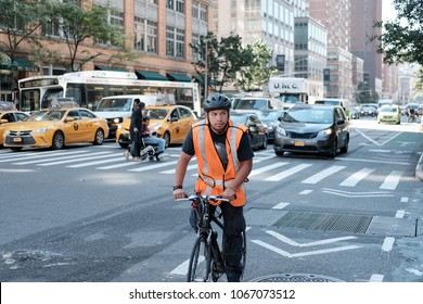 New York City, NY, USA - Circa October 2016: Young male cyclist seen wearing a high vis jacket and bike helmet, waiting at a busy junction with traffic behind him near a crossing area.