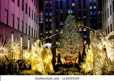 New York City, NY / USA - 12 23 2013: angels with big christmas tree with light in front of the Rockefeller center. Christmas famous decorations in Midtown, Manhattan in the New York City downtown.