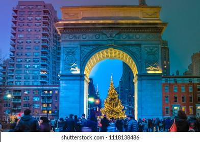 New York City, NY / USA - 12 25 2013: People are walking during Christmas time at Washington Square in Manhattan at dusk / night in front of the Christmas tree with night lights.