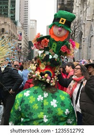 New York City, NY, USA- April 1, 2018: A woman in a costume decorated in an Irish theme of shamrocks and leprechauns walks down Fifth Avenue during the annual Easter Bonnet Parade.