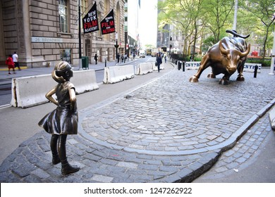 New York City, NY / USA - May 8 2018: The Fearless Girl facing the Charging Bull in the financial district of lower Manhattan.
