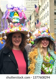 New York City, NY, USA: April 21, 2019:  Two women with elaborately decorated Easter hats participate in the annual Easter Bonnet Parade on Fifth Avenue.