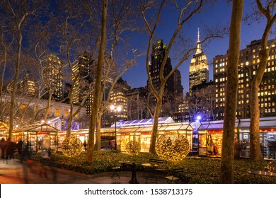 New York City, NY, USA - December 11, 2018: Bryant Park Winter Village (Christmas Market) in evening with the Empire State Building in the background. Midtown, Manhattan