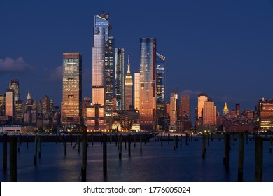 New York City, NY, USA - July 12, 2019: The Hudson Yards skyscrapers with the Empire State Building at Dusk. Manhattan Midtown West cityscape from across the Hudson River
